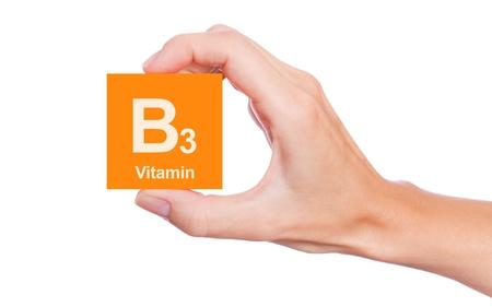 Hand, die ein Feld von Vitamin B3 hält isoliert auf weißem Hintergrund