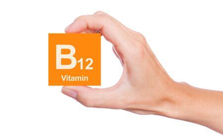 Hand, die ein Feld von Vitamin B12 auf weißem Hintergrund hält Lizenzfreie Bilder