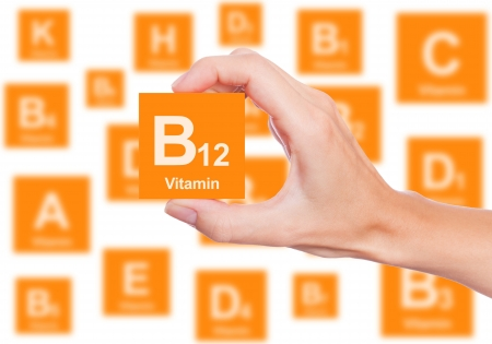 and vitamin: Hand holds a box of vitamin B12