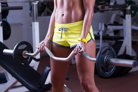 Girl with a sexy body lifting weights at gym photo