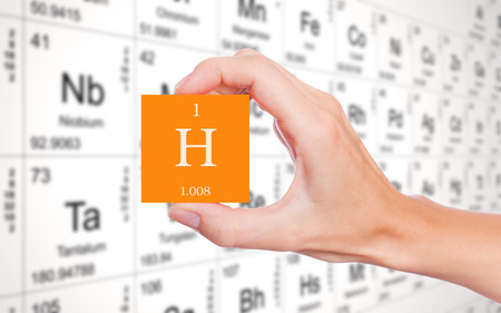periodic table: Hydrogen symbol handheld in front of the periodic table Stock Photo