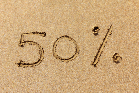 reduction: 50 percent off written on the sandy beach Stock Photo