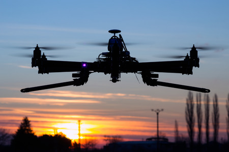 Hexacopter drone flying in the sunset like an UFO
