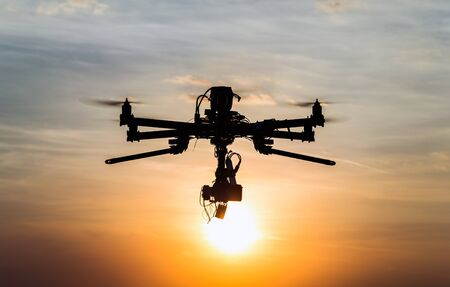 helicopter: Professional drone flying in the sunset Stock Photo