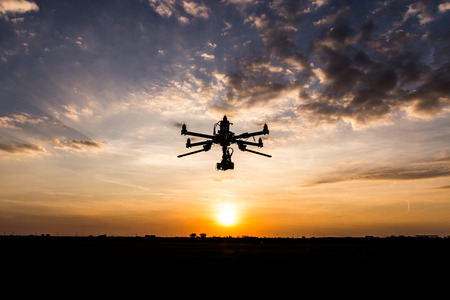professional: Professional drone flying in the sunset Stock Photo