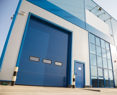 Modern industrial building with big blue garage door