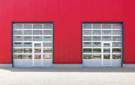 Twee industriële deuren met ramen op rode industriële muur