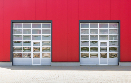 Two industrial doors with windows on red industrial wall