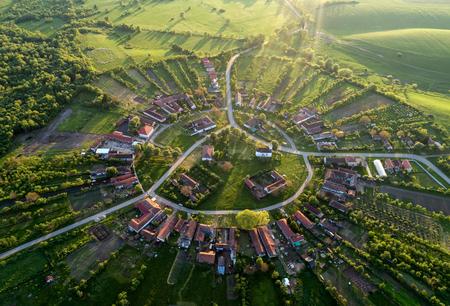 柔らかい素敵なレンズフレアとプロフェッショナルなドローンで夕日を上から見たルーマニアの美しいユニークな円形村 写真素材