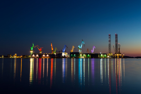 Colorful architectural lighting on giant cranes at night in Pula, Croatia