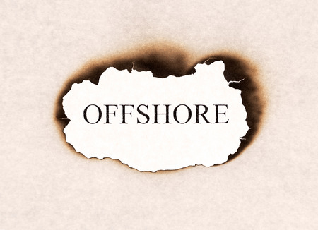 Offshore word text appearing behind burned paper