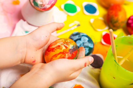 Colorful Easter painted egg in cildren hands hands over the work table