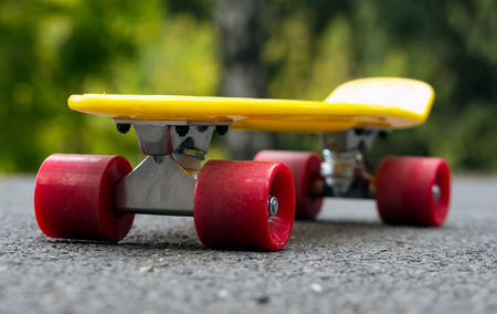 Yellow skateboard with red wheels on asphalt