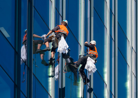 Window washers cleaning the glass facade of a skyscraper