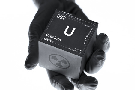 Uranium cube in the hand of a scientist. Radioactive element from the periodic table