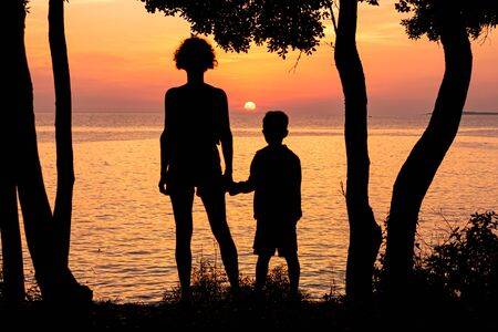 Mother and her child watching beautiful sunset on the seashore