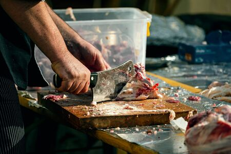 The butcher cuts a piece of meat with sharp cleaver knife at food festival