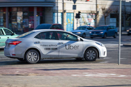 Warsaw, Poland - February, 2019: A gray car with a logo of Uber taxi cab company on it a door is seen in Warsaw.