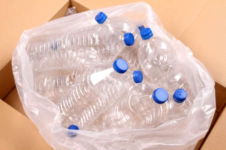 Rubbish bag with bottles of water for recycling inside a cardboard box   photo