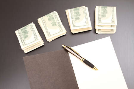 Lots of dollars with an open copybook  photo