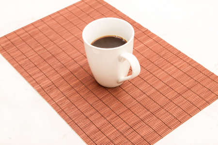 steamy: A steamy cup of coffee on a placemat