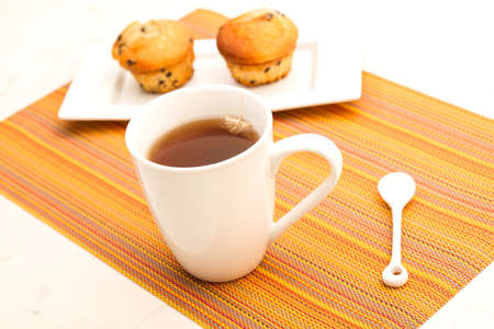 Vanilla with chocolate chips Muffins on a white plate with  a cup of tea  photo