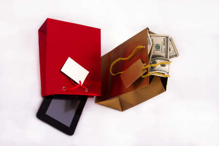 A red gift bag with a Tablet PC and a gold gift bag with dollars, isolated  photo