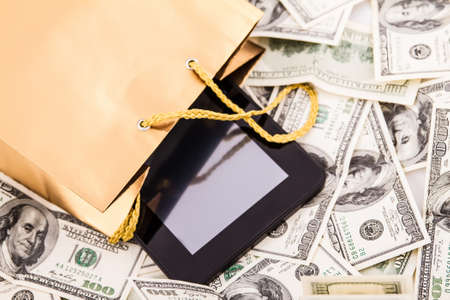 A gold gift bag with a Tablet PC and dollars isolated  photo