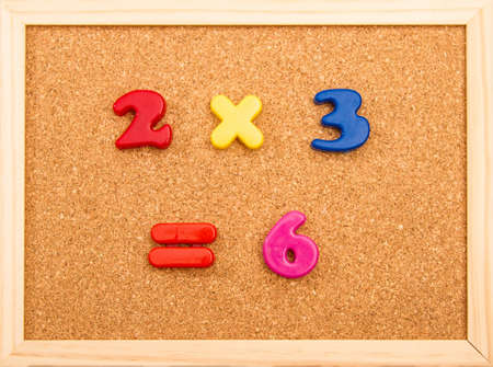 multiplication: Simple mathematic multiplication on a wooden frame cork board