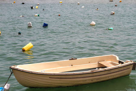 Wooden rowboat in the sea surrounded by plastic containers  photo