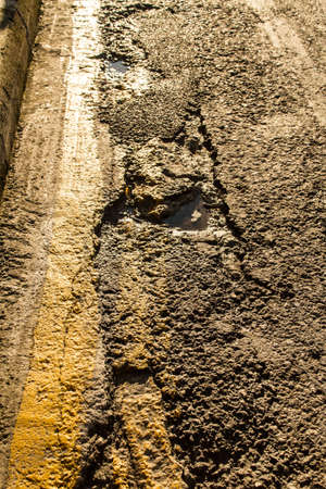 Black broken road surface with a yellow line photo