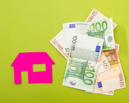 investment real state: Una casa cerca de una pila de euros