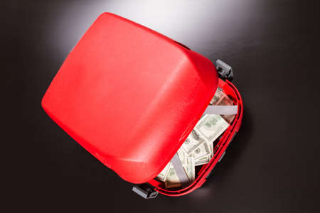spending full: A Suitcase with lots of dollars Stock Photo