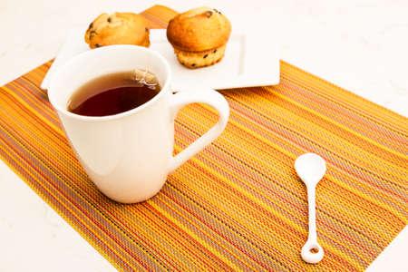 Vainilla con chispas de chocolate Molletes en un plato blanco con una taza de té