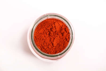 Paprika powder in a glass pot isolated on white   Stock Photo