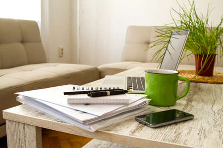 teleworker: Working with a pile of papers and a laptop  Stock Photo