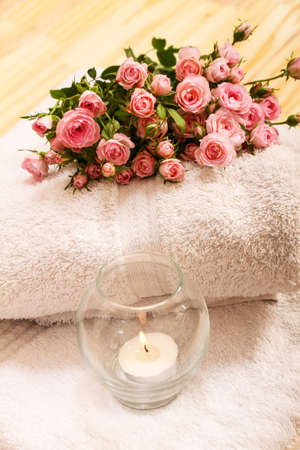 Bunch of small pink Roses on towels with a candle, close up. Stock Photo - 27144747