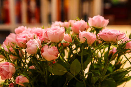 Bunch of small pink Roses in a glass vase over a wooden table.  photo