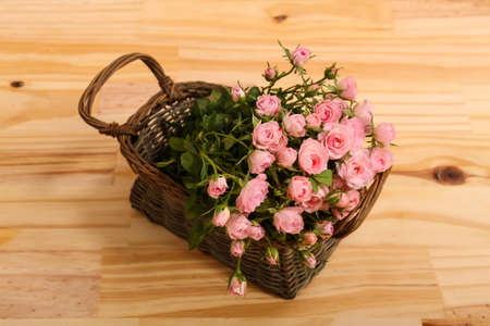 Bunch of small pink Roses in a basket over a wooden table.  photo