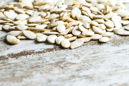 Many pumpkin seeds on a wooden table, background  photo
