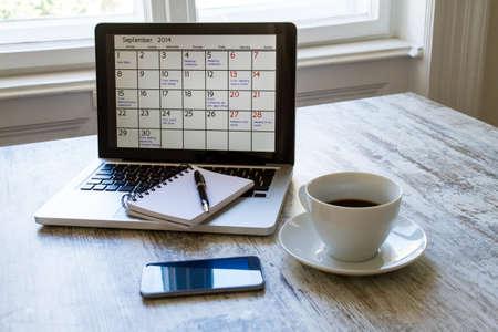 calendrier: V�rification des activit�s et des rendez-vous mensuels au bureau de l'ordinateur portable Banque d'images