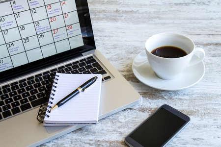 Het controleren van de maandelijkse activiteiten en afspraken op het kantoor in de laptop Stockfoto