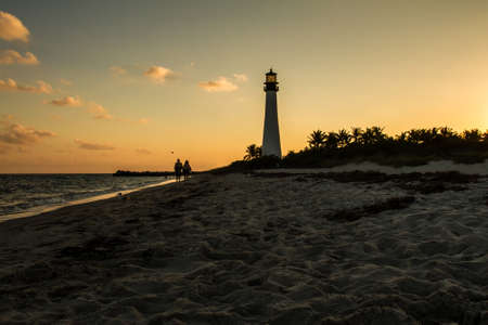 bill baggs: A couple walking in the beach of the Lighthouse on sunset at the Florida State Park, Key Biscayne, Miami, United States