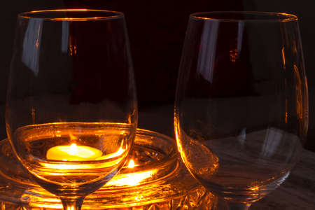 Two wineglasses empty, illuminated by a candlelight photo