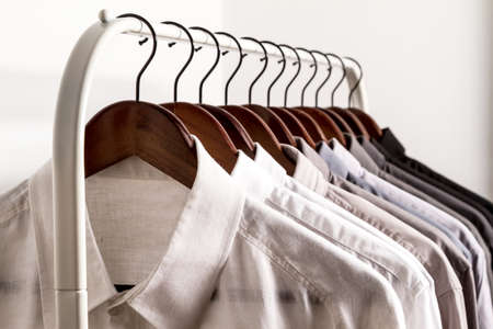 Several shirts on a hanger from white to black color range Foto de archivo