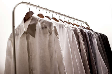 Several shirts on a hanger  from white to black color range Stock Photo