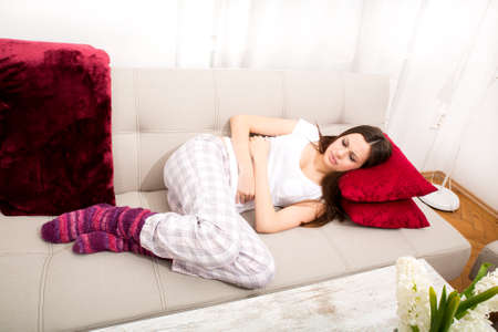 stomachache woman: Young woman in the sofa with period pain