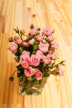 glass vase: Bunch of small pink Roses in a glass vase over a wooden table. Stock Photo