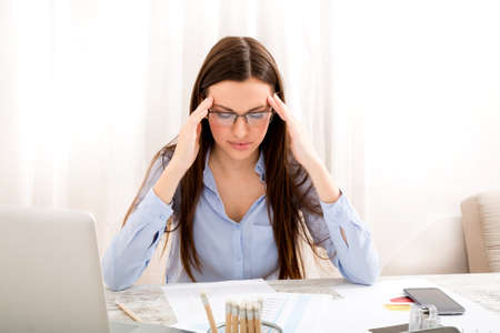 migraine: Having a headache after working really hard Stock Photo