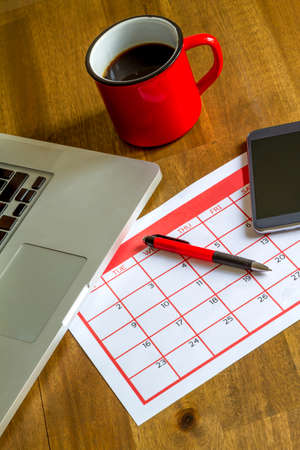 personal goals: Working with the laptop and organizing monthly activities and appointments in the calendar Stock Photo
